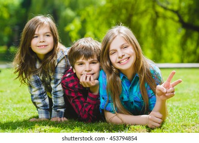 Smiling kids having fun at grass. Children playing outdoors in summer. teenagers communicate outdoor