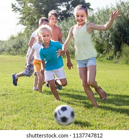smiling kids having fun and kicking football in park on summer day