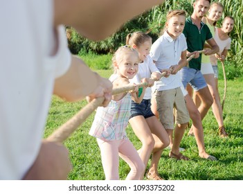 Smiling kids with moms and dads playing tug of war during joint outdoors games on sunny day