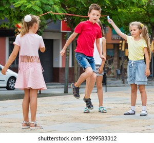 Smiling kids in school age playing together with jumping rope outdoors