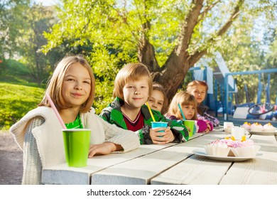 Smiling kids sit together at white table with cups
