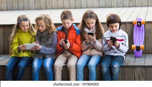 Smiling kids sitting with mobile devices in street