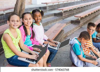 Smiling kids sitting on bench and using laptop at school