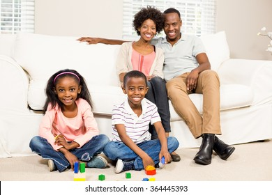 Smiling kids sitting on the floor next to their parents