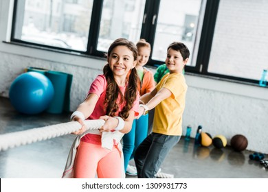 Smiling kids in sportswear pulling rope in gym