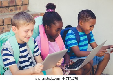 Smiling kids using a laptop and digital tablet on stairs at school