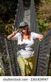 Smiling Kiwi woman on DOC swingbridge tramping in national park