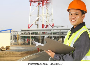Smiling l engineer oil refinery recording technical data on clipboard
