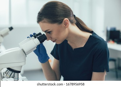 Smiling lab technician in rubber gloves looking confident while using a modern microscope