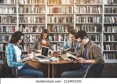 Smiling ladies and glad males looking through information in volumes while sitting at table. They working with gadgets and tasting mugs of liquid