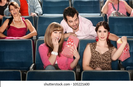 Smiling ladies sharing popcorn with man in theater