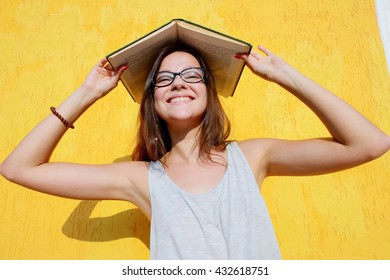 smiling lady with book on a head