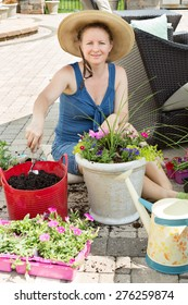 Smiling lady gardener potting up spring flowers in ornamental arrangements as she sits in the shade on a brick patio on a hot spring day with her nursery seedlings and potting soil