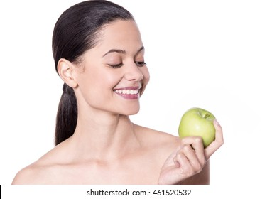 Smiling lady with healthy skin holding green apple