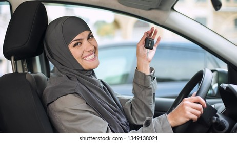 Smiling lady in hijab showing car key in camera, buying new auto driving license