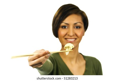 Smiling lady holds a piece of cooked cauliflower with chopsticks.