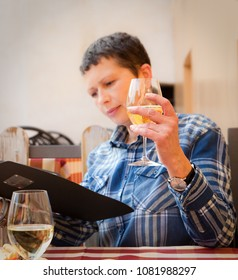 Smiling lady reading menu and drinking white wine,  glass