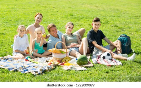 Smiling large family of six having picnic outdoors on green lawn in park