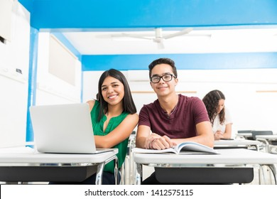 Smiling Latin classmates sitting together in lecture at high school