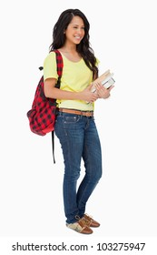 Smiling Latin student with backpack holding textbooks against white background
