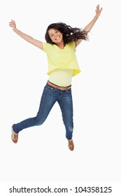 Smiling Latin student jumping against white background
