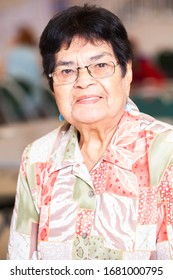 Smiling Latina woman in a busy senior center