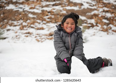 Smiling Latino girl sitting on snow covered mountain, making a snowman and wearing winter clothes.