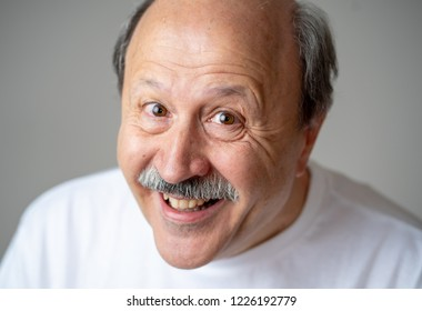 Smiling and laughing 60s year old senior man candid close up portrait in human emotions and facial expressions concept isolated in neutral background.