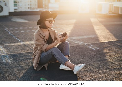 Smiling and laughing young model teenager or woman in hipster outfit, glasses and fedora hat holds vintage analog photo camera, sits on top of rooftop during summer sunset
