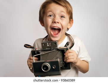 smiling , laughing,boy,young child ,photographer holding a instant camera on a white background