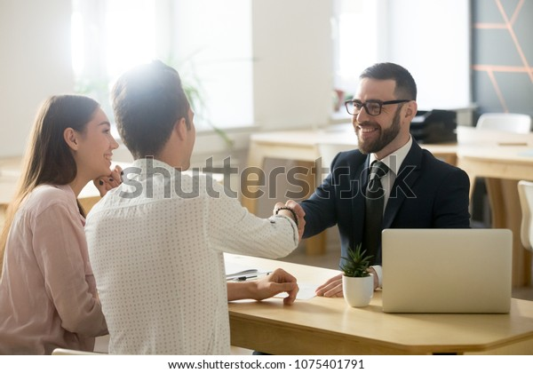 Smiling lawyer, realtor or financial advisor handshaking young couple thanking for advice, insurance broker or bank worker and millennial customers shake hands making deal, investment or taking loan