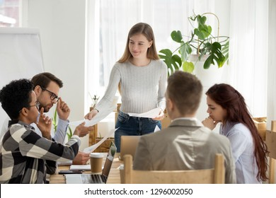 Smiling leader coach mentor giving new business plan handout to diverse employees team at group meeting, female manager leading corporate training handing paper report to workers discussing paperwork