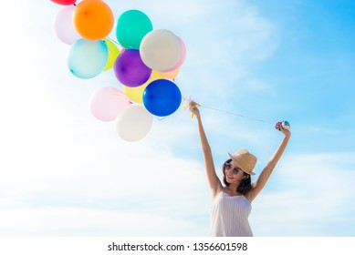 Smiling lifestyle asian woman chill hand holding balloon on the beach. Relax and Enjoy in summer holiday. Summer and Travel Concept