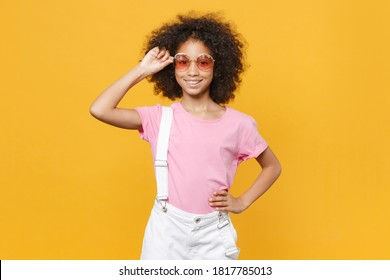 Smiling little african american kid girl 12-13 years old in pink t-shirt eyeglasses isolated on yellow background studio portrait. Childhood lifestyle concept.