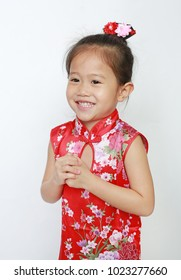 Smiling little Asian child girl wearing red cheongsam with greeting gesture celebration for Chinese New Year isolated on white background.