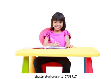 Smiling little asian girl writing on the desk, Isolated over white with clipping path