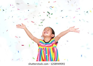 Smiling little Asian kid girl with many falling colorful tiny confetti pieces on white background. Happy New Year or Congratulation Concept.