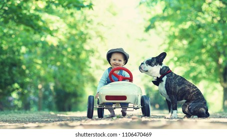 smiling little baby girl in pedal car with her dog