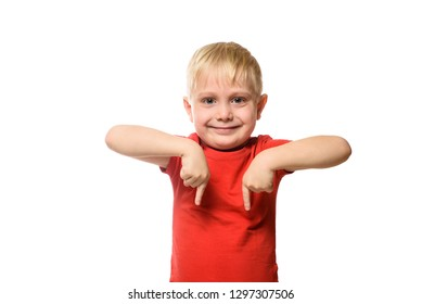 Smiling little blond boy in a red shirt stands and shows index fingers down. Isolate on white background