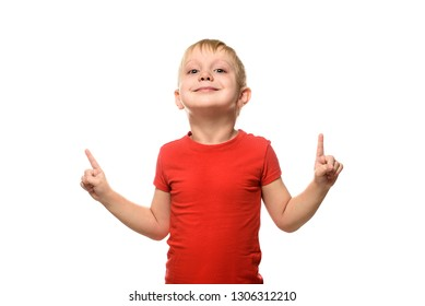Smiling little blond boy in a red T-shirt is standing and pointing with his index fingers upwards. Isolate on white background