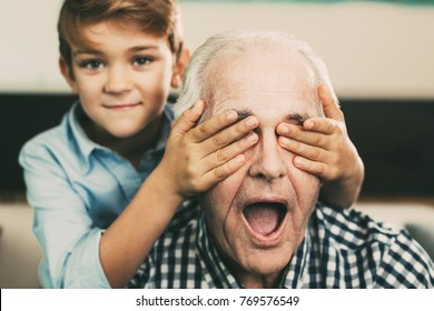 Smiling little boy covering eyes of grandfather