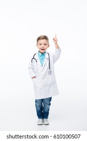 Smiling little boy in doctor costume pointing up with finger  isolated on white