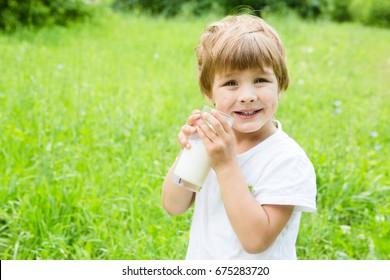 Smiling little boy drink milk on the green meadow.