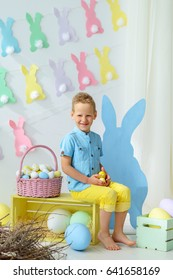 smiling little boy in easter decorations.Kids celebrate Easter.  Home decoration, pastel bunny banner, colorful Easter eggs and flowers.