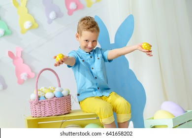 smiling little boy in easter decorations,The boy is holding Easter eggs.Kids celebrate Easter.  Home decoration, pastel bunny banner, colorful Easter eggs and flowers.