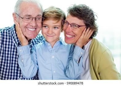 Smiling Little Boy Embracing Grandparents