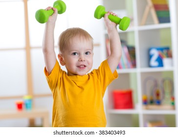 Smiling little boy exercising with dumbbells. Healthy life and sport concept.