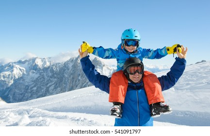 Smiling little boy with father in the mountains during ski holiday.