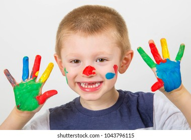 smiling little boy with hands painted in colorful paints