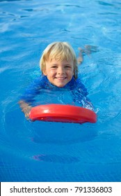 Smiling little boy has fun with floating board  in  swimming pool